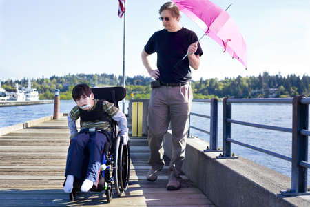 special needs: Father walking with disabled six year old son in wheelchair out on lake pier on sunny day