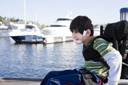 Disabled biracial six year old boy pushing himself in wheelchair on lake pier