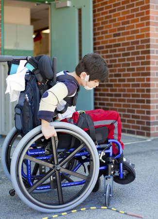 Uitgeschakeld kindergartener proberen rolstoel manuever op speelplaats in de pauze