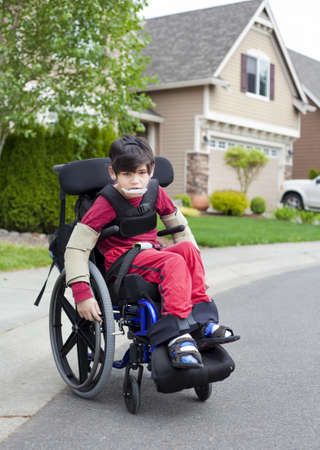 Disabled biracial six year old boy sitting in wheelchair on sidewalk Stock Photo - 20019842