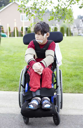 Disabled biracial six year old boy sitting in wheelchair on sidewalk