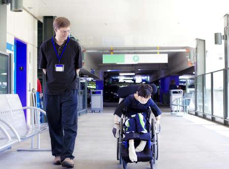 enfants handicap�s: P�re marchant avec le fils handicap� dans un fauteuil roulant que lui-m�me les roues dans l'entr�e de l'h�pital