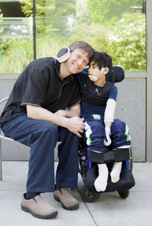 disabled person: Disabled six year old boy in wheelchair hugging father while waiting at hospital