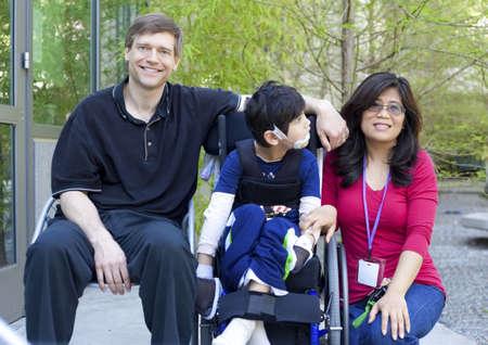 ni�os discapacitados: Desactivado birracial ni�o de seis a�os en silla de ruedas con los padres al aire libre