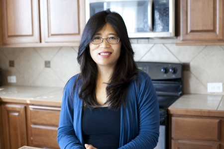 Beautiful Asian woman in early forties standing in kitchen, stove and cabinets in background