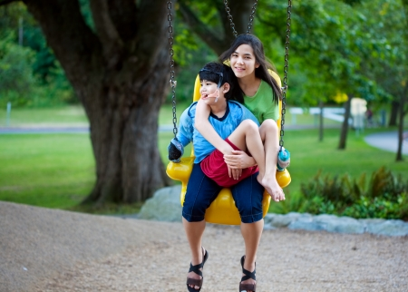Big sister holding disabled brother on special needs swing at playground in park. Child has cerebral palsy.