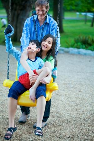 Grande sorella azienda fratello disabile su esigenze particolari altalena al parco giochi nel parco, come il padre spinge. Bambino ha paralisi cerebrale. Archivio Fotografico - 22478132