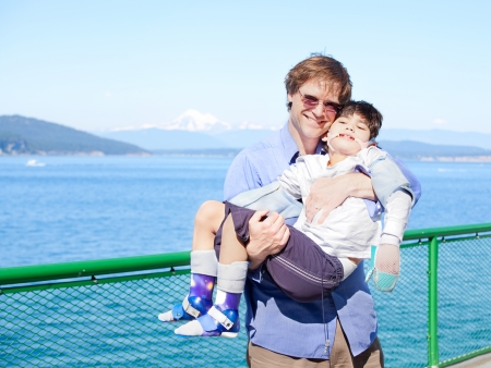 Father holding disabled son in arms on deck of ferry boat. Puget Sound in background. Child has cerebral palsy.