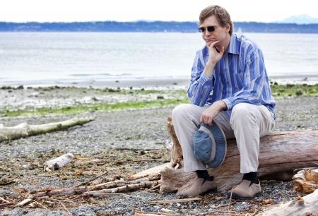 Depresso, triste uomo caucasico in quarantina seduto su legni sulla spiaggia, il mento in mano