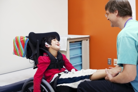Disabled boy in wheelchair sharing laugh with his doctor or therapist