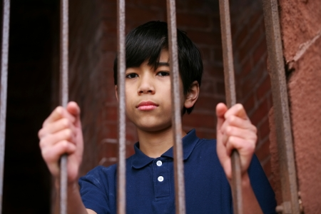 Boy standing behind bars, sad  or wary expression. Illustration purposes.