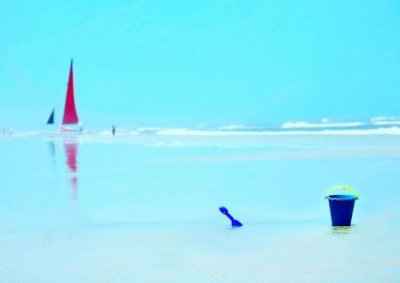 Ontspannend Strandscenario met zeilboot, emmer en schop Stockfoto