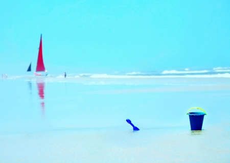 Relaxing Beach scenario with sailboat , bucket and shovel