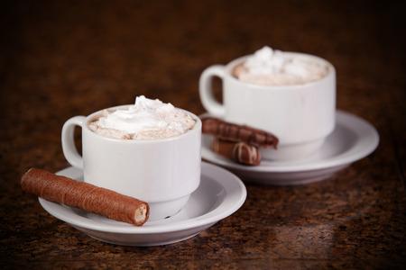 Twee kopjes koffie of warme chocolademelk met chocolade en koekjes op bruine achtergrond