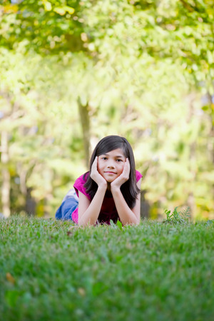 Ten year old girl lying down on grass, chin in hand