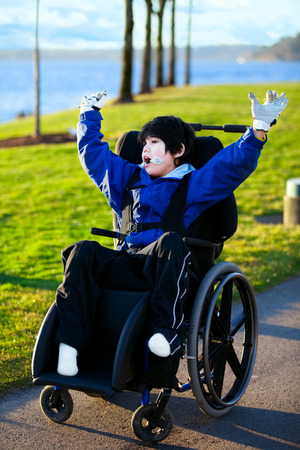 Disabled boy in wheelchair enjoying day at park, arms raised in happiness