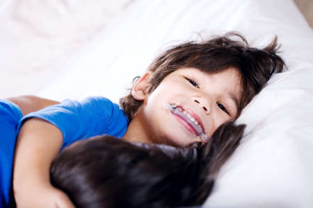 Disabled little boy hugging sister on bed Stock Photo - 29209074