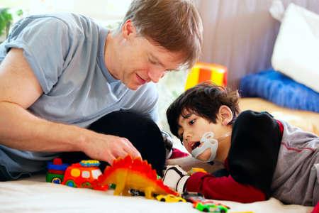 niños discapacitados: Padre hermoso que juega coches con el hijo con discapacidad en la estera de piso