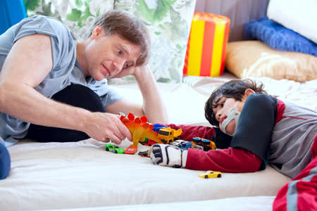 Handsome father playing cars with disabled son on floor mat photo