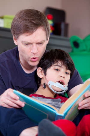 Father reading book with disabled son Stock Photo - 29209094