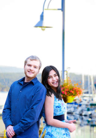 Happy young  interracial couple standing back to back on boat pier photo
