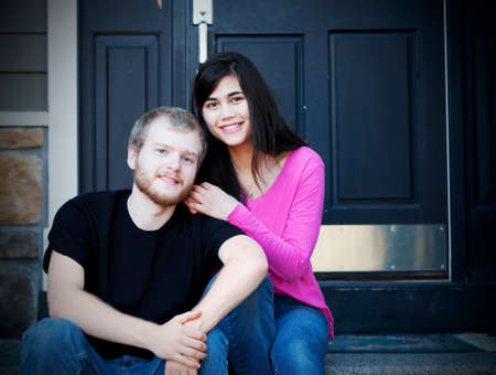 Happy young interracial couple sitting on front steps of home