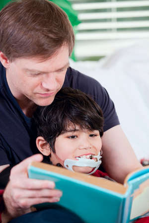Father reading book with disabled son photo