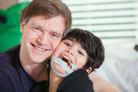Handsome father holding disabled seven year old son, smiling together Stock Photo - 29386861
