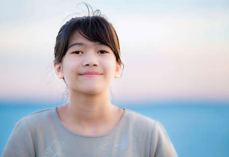 preteen girl: Beautiful biracial young preteen girl enjoying outdoors by lake at sunset