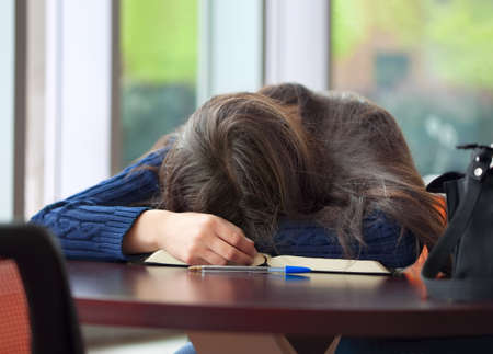 tired: Tired student asleep at school table, head on book