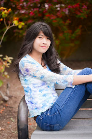 Young biracial preteen girl ejoying outdoors, sitting on wooden park bench Stock Photo