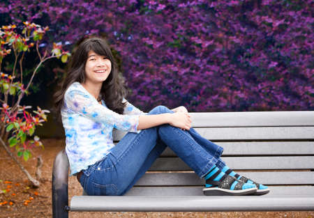 preteen asian: Young biracial preteen girl ejoying outdoors, sitting on wooden park bench Stock Photo