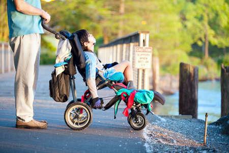Padre con il figlio disabile in sedia a rotelle al parco all'aperto, godendo del tramonto Archivio Fotografico - 29386895