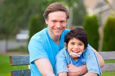 Handsome father sitting with smiling disabled seven year old son outdoors photo
