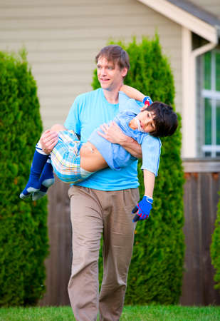 Father carrying disabled seven year son outdoors photo