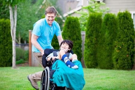 ni�o empujando: Padre que se ejecuta con el hijo lisiado en silla de ruedas