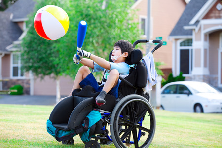 Disabled little boy playing ball in the park