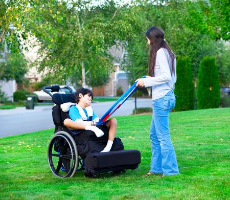 Biracial ältere Schwester, die draußen spielen mit behinderten kleiner Bruder im Rollstuhl Standard-Bild - 34156304