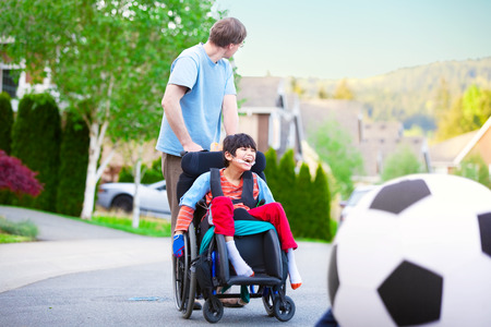 Caucasian father helping disabled biracial son in wheelchair play soccer outdoors on street