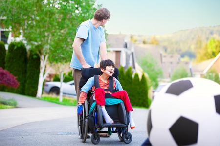 Padre caucásico ayudar a discapacitados hijo birracial en el juego de ruedas fútbol al aire libre en la calle Foto de archivo - 34145518