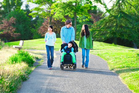 Disabled boy in wheelchair walking with family outdoors on sunny day in park Foto de archivo