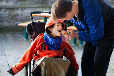 Father feeding disabled son a hamburger in wheelchair. Child has cerebral palsy Stockfoto