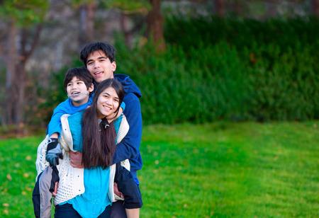 Behinderte biracial Kind Reit Huckepack auf seine Schwester, Familie ihn umgebenden zusammen im Park. Standard-Bild - 35848754