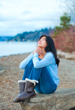 Young biracial teen girl in blue shirt and jeans sitting on boulder or rock  along lake shore praying, face upward to sky