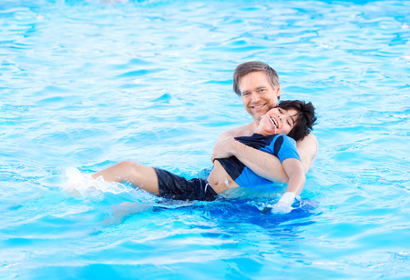 Caucasian father swimming in pool with biracial disabled son in his arms. Child has cerebral palsy. Stock Photo