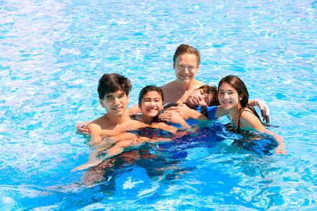 多民族の家族はプールで一緒に泳ぐ。無効になって息子が脳性麻痺です。 写真素材