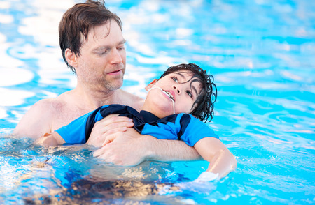 Caucasian father swimming in pool with biracial disabled son in his arms. Child has cerebral palsy. Stockfoto