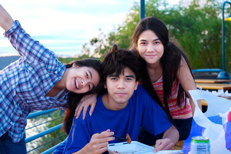 Brother and sisters outdoors in group hug, dining and hanging out