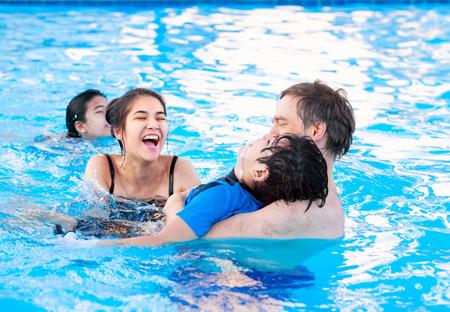 Multietnico famiglia di nuoto in piscina. Figlio minore disabile ha paralisi cerebrale.