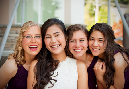 Beautiful biracial young bride smiling with her multiethnic group of bridesmaids in purple dresses, heads together Stock Photo